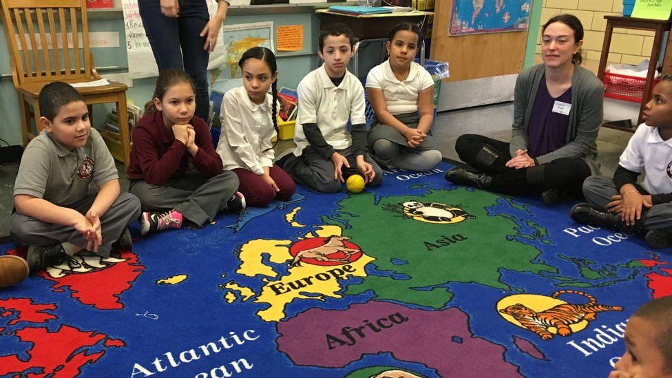 Children sit on a colorful rug decorated with a map and animals.