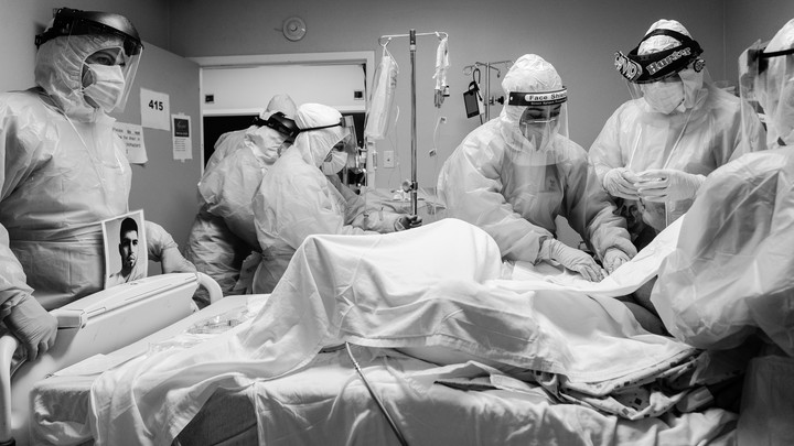Doctors wearing PPE surrounding a coronavirus patient.