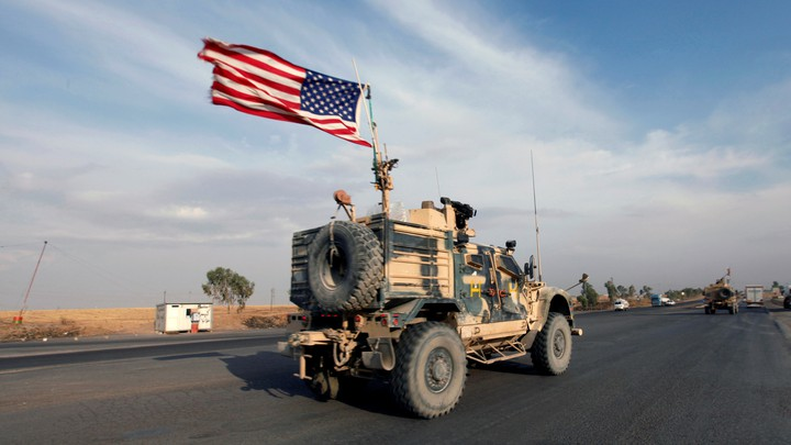 A convoy of U.S. military vehicles travels down a road in Iraq.
