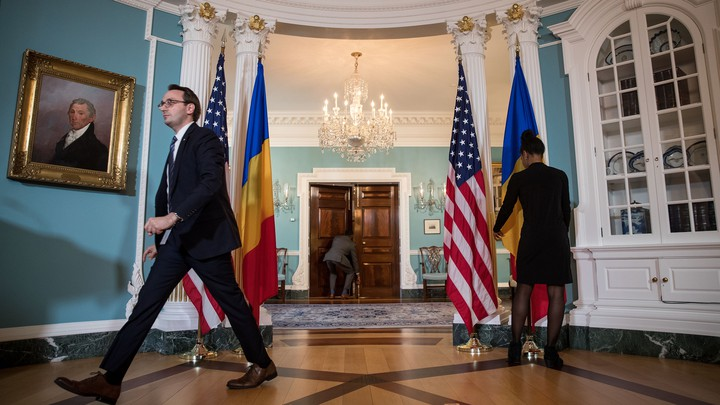 State Department staffers prepare the blue Treaty Room for a visit from the Romanian president.