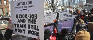A photo of protesters carrying anti-Amazon posters during a rally and press conference in NYC.