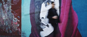 A man walks by a brightly colored mural of activist Malala Yousafzai in Bushwick, a neighborhood in Brooklyn, New York.