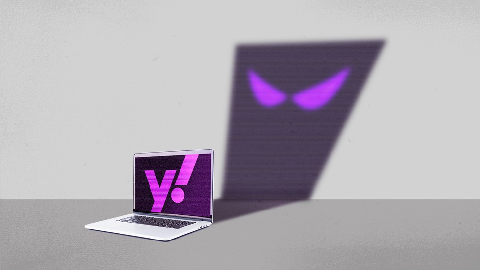 A laptop with a Yahoo logo on the screen, casting the shadow of a cartoon ghost