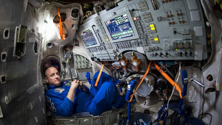 Scott Kelly in a blue NASA space suit at a control panel on the International Space Station
