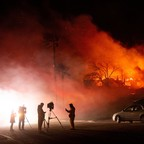 Photo: Media members report on a burning home as a firefighter douses flames during the Hillside fire in the North Park neighborhood of San Bernardino, California on October 31, 2019.