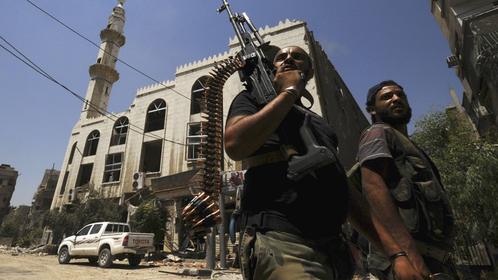 Two men with guns walk down a street in Syria.