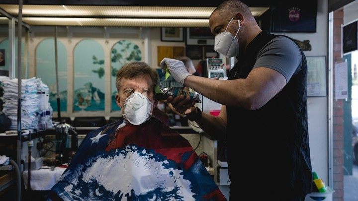 A stylist wearing a protective mask cuts a customer's hair at a barbershop in Atlanta.
