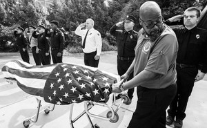 A man wheels the flag-covered body of a firefighter who died of COVID-19 past saluting officers.