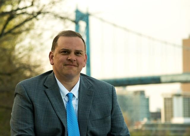 Mayor Wade Kapszukiewicz, with a bridge behind him