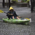a photo of a man paddling his kayak down a flooded street in Charleston following Hurricane Dorian.