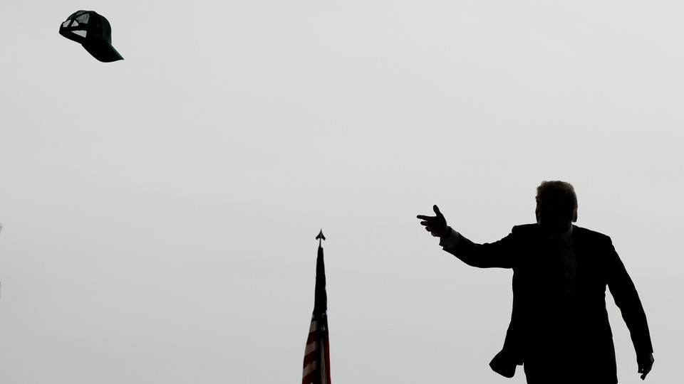 A silhouette of Donald Trump throwing a hat into a crowd