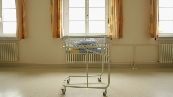 Folded blankets sit atop a cart that holds newborn babies