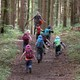 Kids with backpacks running up a forest trail