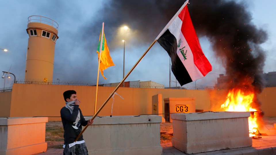 A protester holds an Iraqi flag outside the main gate of the U.S. embassy in Baghdad on December 31.