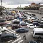 A man crosses a street during a traffic jam on the embankment of the Moskva River in downtown Moscow.