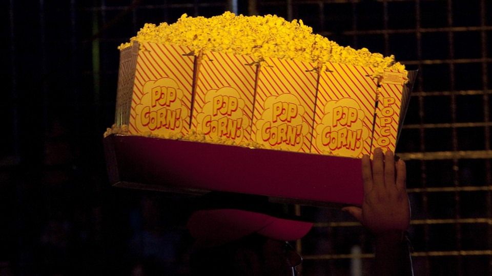 A vendor carries large bags of popcorn on a tray above his head.