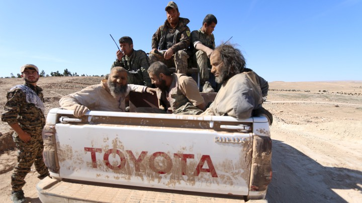 Syrian Democratic Forces soldiers transport captured Islamic State fighters in a pickup truck in Syria in 2016.