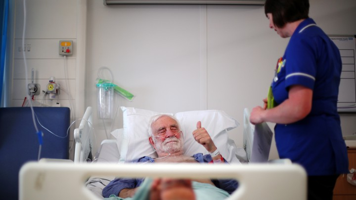 "A man giving the ""thumbs-up"" sign in a British hospital bed"