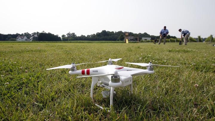 A DJI Phantom 2 drone sits on grass.