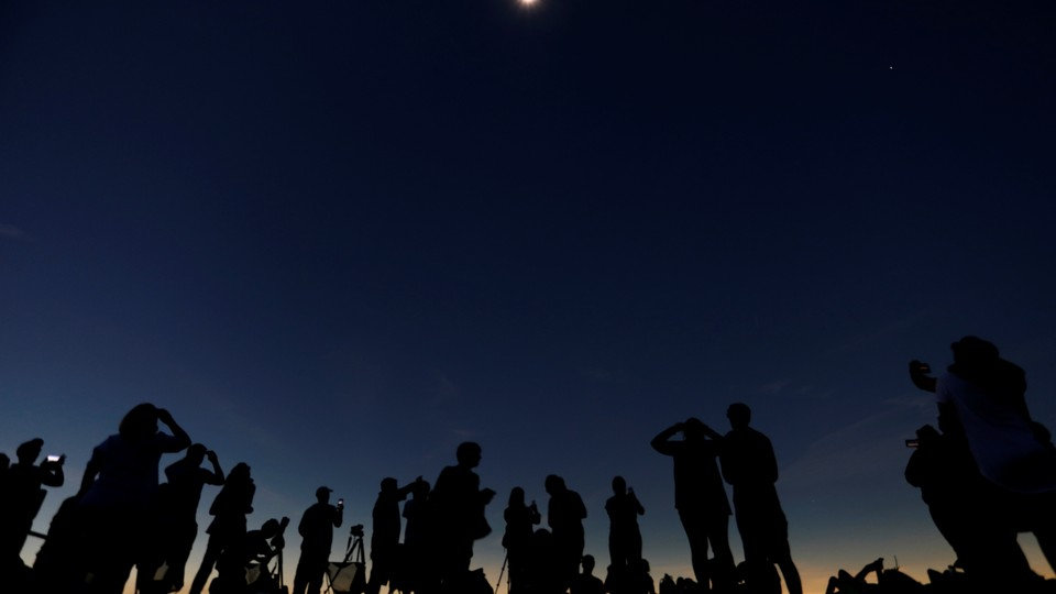 A group of people watches a solar eclipse.