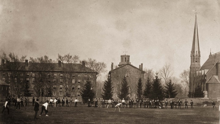 People stand on Wesleyan's college quad, near the campus's gothic Memorial Chapel.