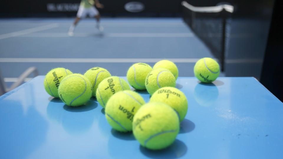 Eleven tennis balls near a tennis court