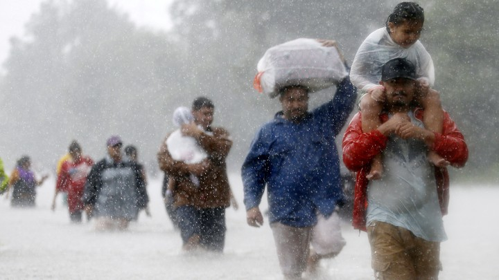Houston residents wade through floodwaters and heavy rain.