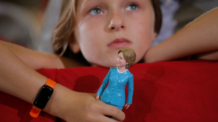 Belle Shefrin, 9, holds a doll of Hillary Clinton while listening to Clinton speak at a campaign rally in Ohio in 2016.