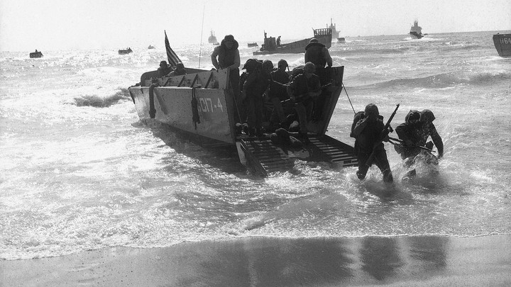 Marines in the process of disembarking from a ship onto a beach.