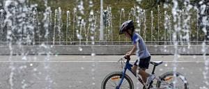 A kid rides a bike through a fountain