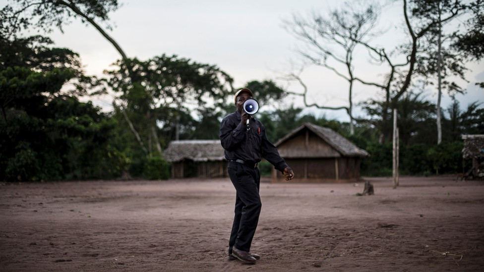 A health worker holds a megaphone to his mouth while standing on a patch of dirt.