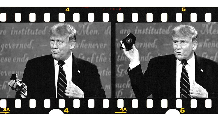 Trump gestures with a mask in his hand