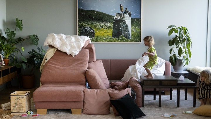 A child stands on a table, staring at a recently-made pillow fort.