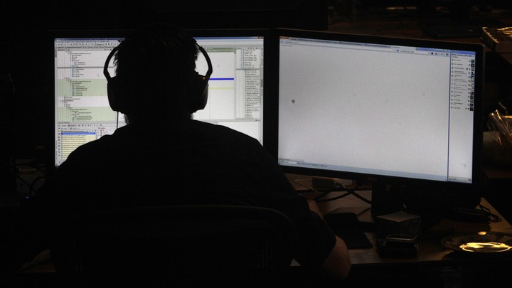 A person wearing headphones in silhouette, backlit by the light of two computer screens with code