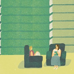 Two women sit in comfortable armchairs, in front of a wall of giant books