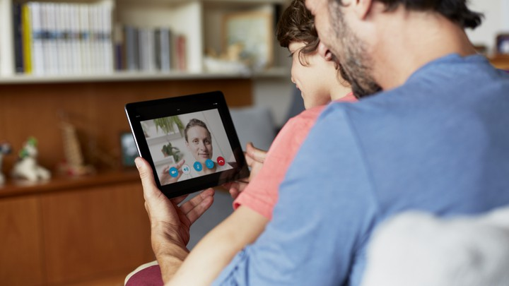 A father and son chat use Skype to video chat
