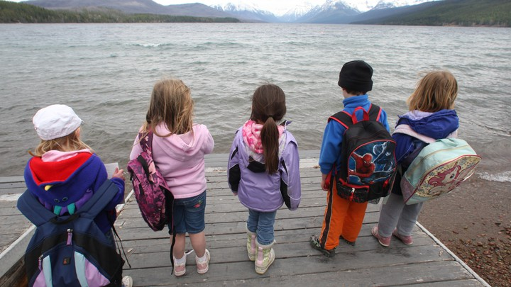 Five children holding backpacks look out at the expansive lake and mountains of Glacier National Park.