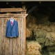A suit and dress hanging on a barn wall next to hay bales