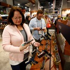 People handle guns on display at a show in Las Vegas.