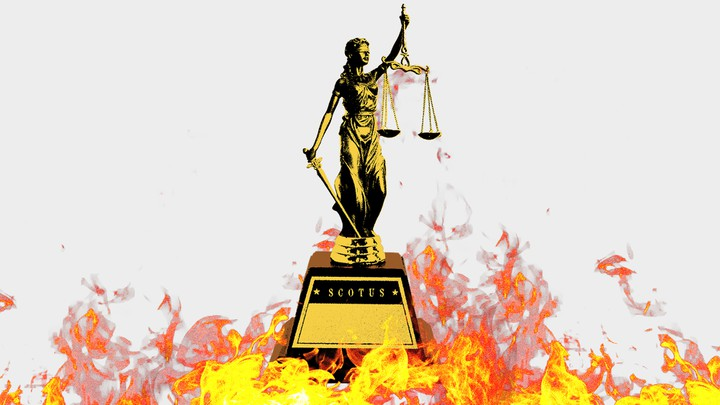 A statue of lady justice is surrounded by flames.