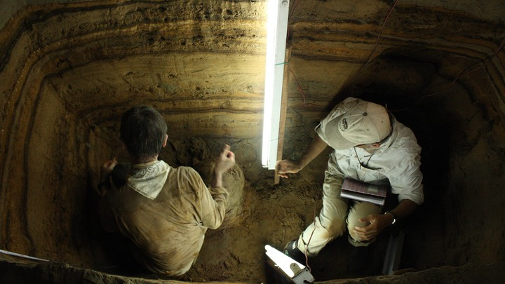 Kerry Sieh and Charles Rubin use fluorescent lights to look for charcoal and shells for radiocarbon dating.