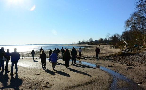 People walk along a shore with small streams of water going to the sand.