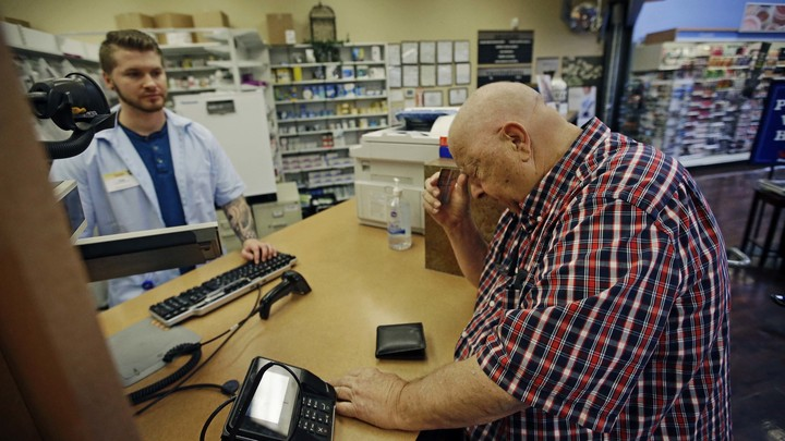 A man picks up prescriptions at a pharmacy.
