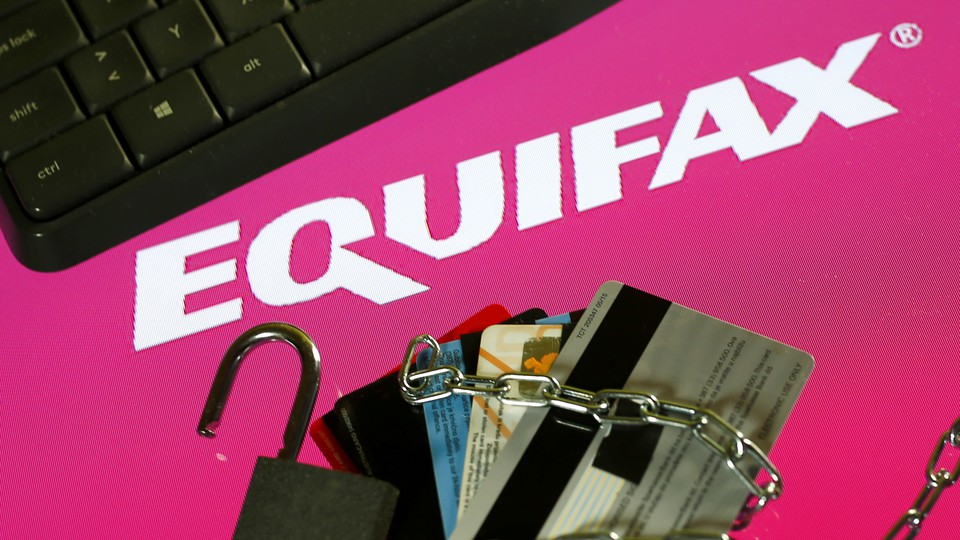 A keyboard, credit cards, chain, and padlock next to the Equifax logo