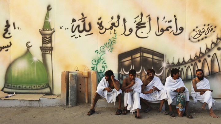 Muslim pilgrims rest in front of a mural depicting the Kaaba in the Grand Mosque during the haj pilgrimage.