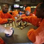 Black men in orange jumpsuits playing chess.