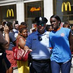 A fast-food worker is detained by police outside a McDonalds during a protest for a higher minimum wage.