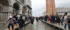 Tourists walk on raised platforms during a period of seasonal high water in Venice in February 2015.