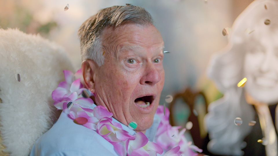 An older man wearing a pink lei surrounded by confetti
