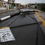 People walk next to fallen electric poles and traffic signs in Salinas, Puerto Rico, after the area was hit by Hurricane Maria.